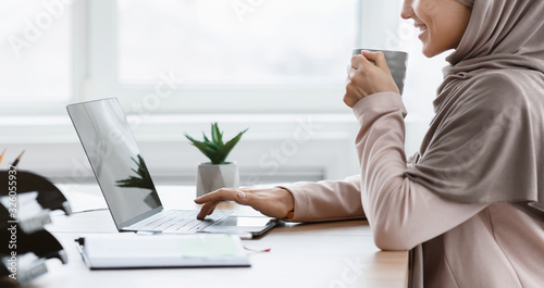 Unrecognizable muslim woman in hijab drinking coffee and typing on laptop Fototapeta
