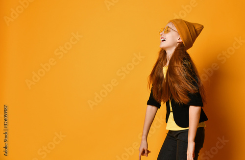 Red-haired girl in stylish sunglasses hat yellow t-shirt and black jacket is lau Wallpaper Mural