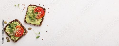 Fototapeta Bright tomato slices decorate sandwiches with avocado spread obraz