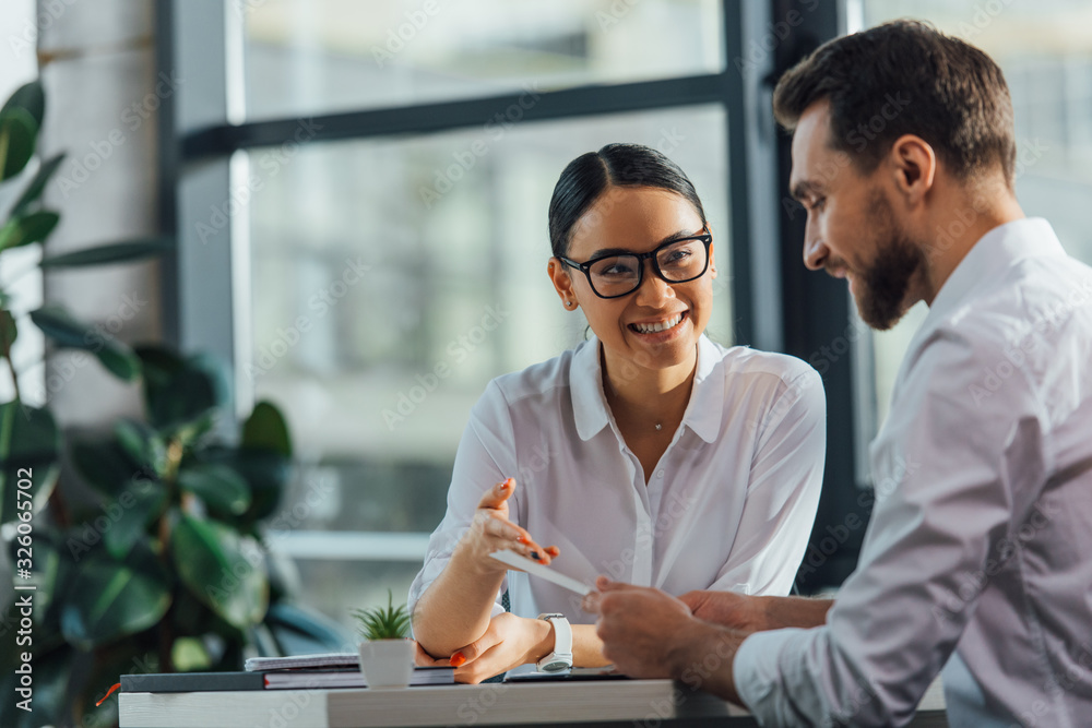Fototapeta female asian translator working working with smiling businesswoman