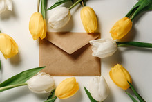 Flat Lay Composition With An Envelope From Craft Paper Among Tulips On A White Background.
