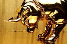 Golden Figurine Of A Bull Bowing Its Head On A Gold Background Close-up.