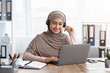 Smiling Arabic Girl Watching Webinar On Laptop While Sitting In Office