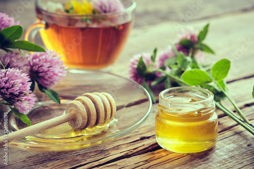 Photographie Clover flowers, healthy, herbal tea cup, honey jar and wooden dipper for honey on table