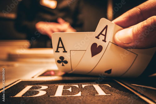 Dealer or croupier shuffles poker cards in a casino on the background of a table, chips Canvas Print