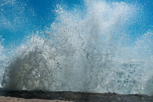 Water Splash Of Powerful Waves On Blue Sky Background. Sea Foam Crashing Close Up , Huge Waves. Water Texture.