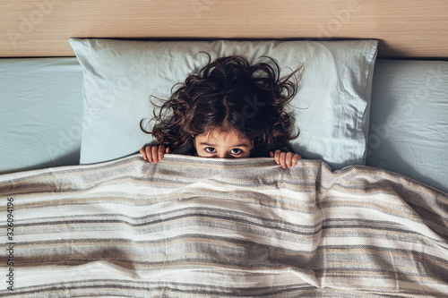 little girl covering her face with the bedspread Canvas Print