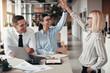Leinwandbild Motiv Laughing businesswomen high fiving together during an office mee