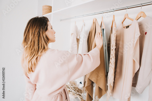 Obraz Cute young woman standing in front of hanger rack and trying to choose outfit. - fototapety do salonu