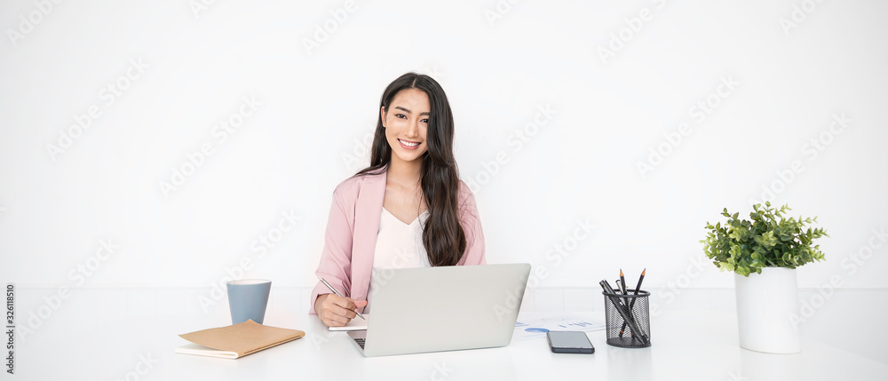 Fototapeta Portrait of smiling beautiful business asian woman in pink suit working in home office desk using computer. Business people employee freelance online marketing e-commerce, work from home concept