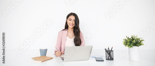 Fototapeta Portrait of smiling beautiful business asian woman in pink suit working in home office desk using computer. Business people employee freelance online marketing e-commerce, work from home concept obraz