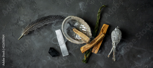 Photo Smudge kit for spiritual practices with natural elements: Palo Santo sticks, dried white sage, Guinea Fowl feather, crystals, sea pearl shell Abalone on a black background