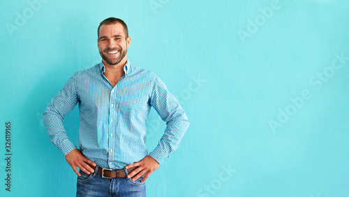 Fototapeta Happy man in front of blue wall with copy space obraz