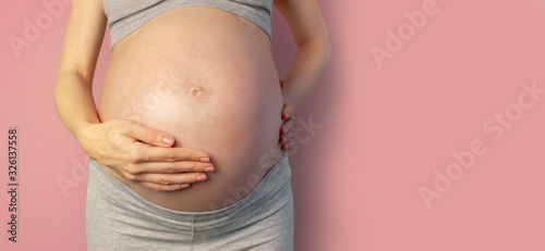 Canvastavla Beautiful young pregnant woman holds hands on her belly on pink background