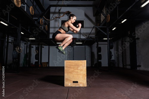 Fényképezés Young strong sweaty fit muscular girl with big muscles doing box jump hardcore c