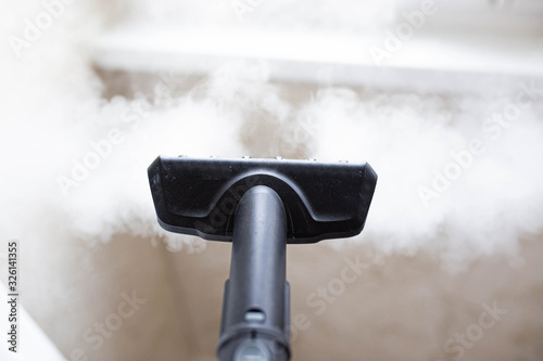 Fototapeta steam cleaner for cleaning the house, steam erupts from the brush. obraz