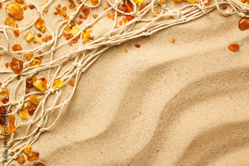 Photo Ambers And Fishing Net Composition On Sand