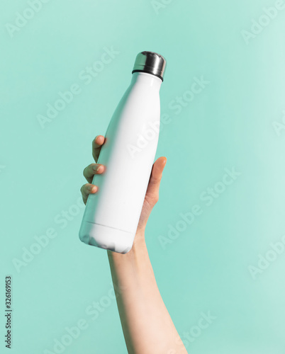 Fotografiet Close-up of female hand holding white reusable steel stainless thermo water bottle isolated on background of cyan, aqua menthe color