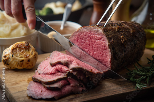sliceing roasted eye of round beef with knife Canvas Print