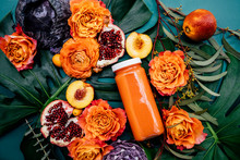Lush Still Life Of Fresh Bottle Of Juice In A Bed Of Colorful Fruits And Flowers