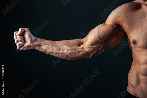 Fotografía tense arm clenched into fist, veins, bodybuilder muscles on a dark background, isolate