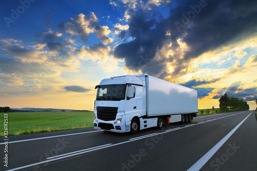 Fotografía White truck transport on the road at sunset and cargo