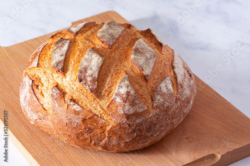 Photo Whole round loaf of artisan sourdough bread on a wooden cutting board