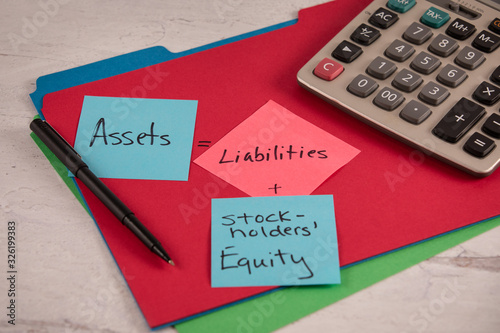 Photo Assets equals liabilities plus stockholders equity notes on red fileing folder p
