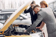 Couple in a car salon. Family buying the car. Elegant woman with her husband. Assistant with a clients