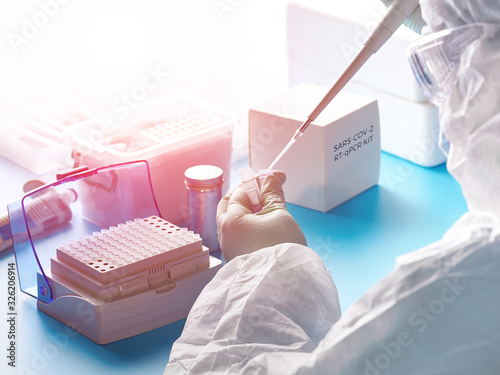 Epidemiologist in protective suit, mask and glasses works with patient swabs to detect specific region of 2019-nCoV virus causing Covid-19 viral pneumonia Canvas Print