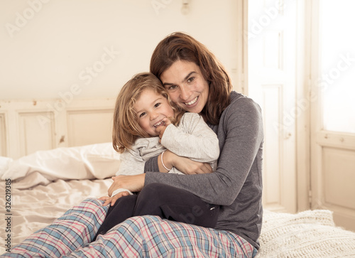 Valokuvatapetti Lifestyle portrait of beautiful mother and daughter relaxing in bed