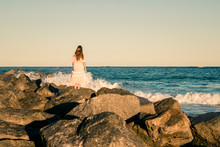 Waves Rolling Against Rocks Where Girl Stands In Golden Light