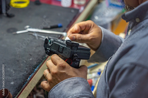 Photo Technician with amputated finger holding tools and cleaning camera's body