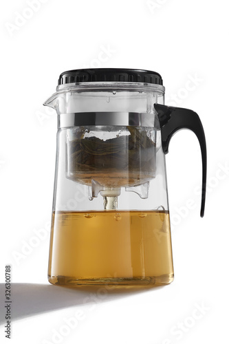 Fototapeta Subject shot of a glass teapot with a removable infuser and inlying strainer, a black handle and cover