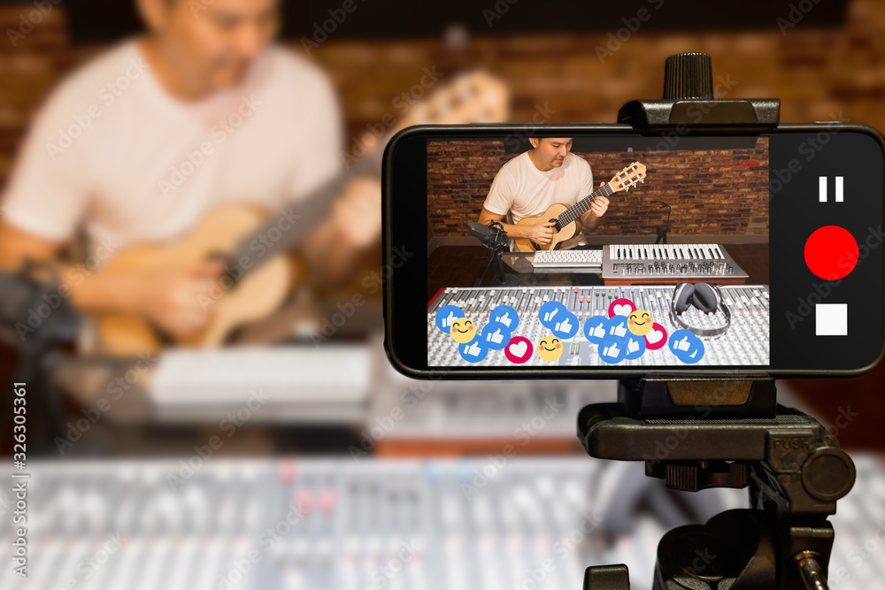 Fototapeta music vlogger streaming a live video while playing acoustic guitar in home studio