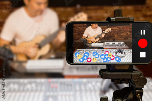 Fototapeta music vlogger streaming a live video while playing acoustic guitar in home studio obraz