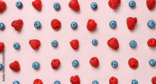 Colorful fruit pattern of raspberries and blueberries on pink background. Flat lay - 326311146