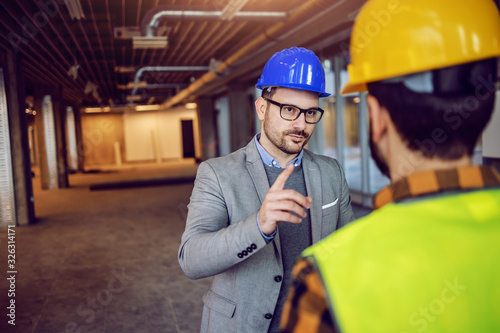Photo Serious Caucasian architect drawing attention to construction worker of importance of project they working on