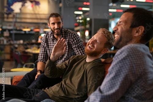 Mid adult men friends enjoying at pub Wallpaper Mural