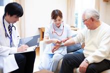 血圧を測る看護師と医...