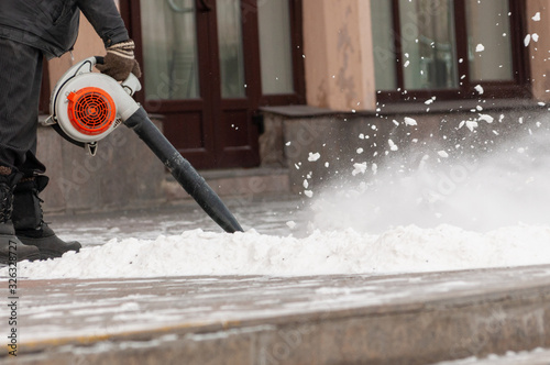 Photo Man cleans street from snow with blower