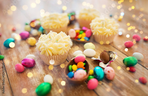 easter, food and holidays concept - close up of frosted cupcakes with chocolate eggs and candies on wooden table