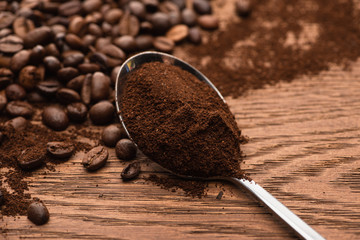 selective focus of fresh roasted coffee beans and ground coffee in spoon on wooden table