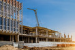 Construction site background. Hoisting cranes and new multi-storey buildings. I.ndustrial background.Building construction site work against blue sky