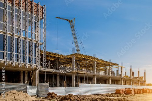 Obraz Construction site background. Hoisting cranes and new multi-storey buildings. I.ndustrial background.Building construction site work against blue sky - fototapety do salonu