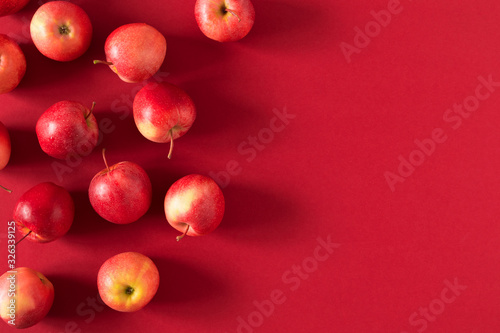 Obraz Red apples on red background. Apples as background. Flat lay, top view, copy space - fototapety do salonu