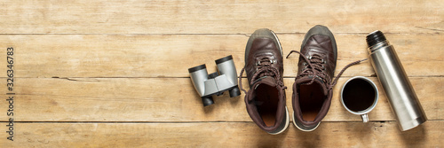 Fototapeta Boots for trail, binoculars, thermos, cup with tea on a wooden background. The concept of hiking, tourism, camp, mountains, forest. Banner. Flat lay, top view obraz