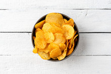 Tasty Potato Chips In Bowl On White Wooden Background. Top View