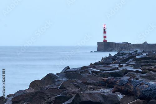 Vászonkép Farol com mar calmo durante o amanhecer e caminho de rochas