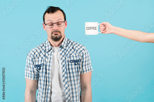 To a sleepy or simply tired man they hold out a large mug of coffee Fototapet